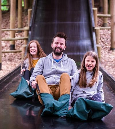 Three people on a slide at BeWILDerwood in Norfolk