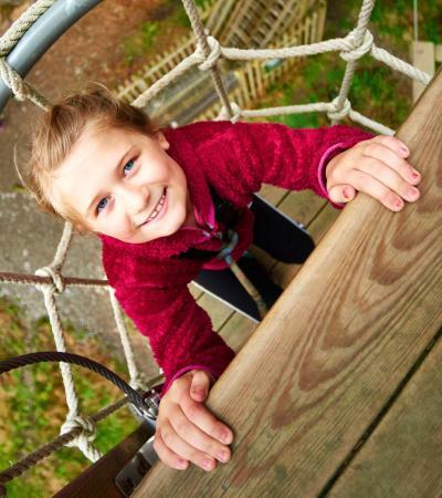 A little girl climbing at Go Ape