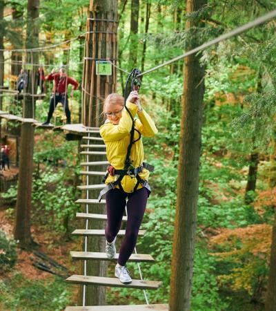 Girl walking across ladder at Go Ape