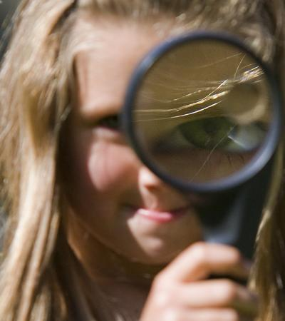 A little girl holding up a magnifying glass on a Treasure Trail