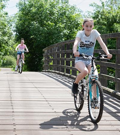Two girls cycling at River Lee Country park