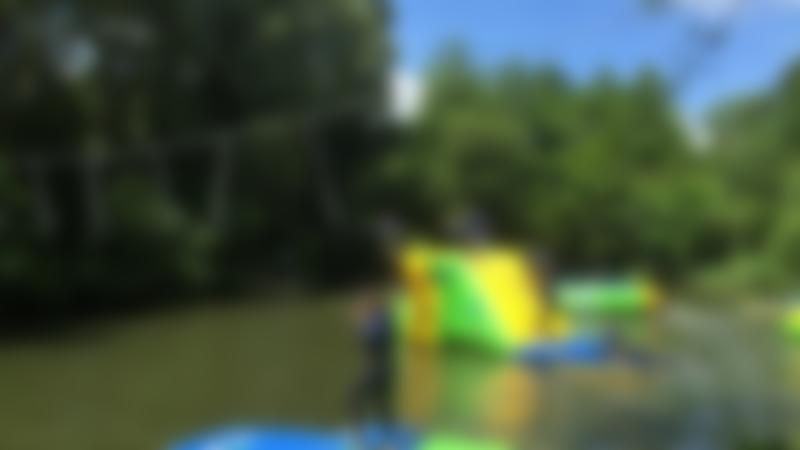 People on inflatable course at Dorset Waterpark in Corfe Castle