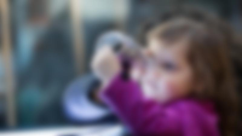 Girl with handmade telescope at Museum of Science and Industry in Manchester
