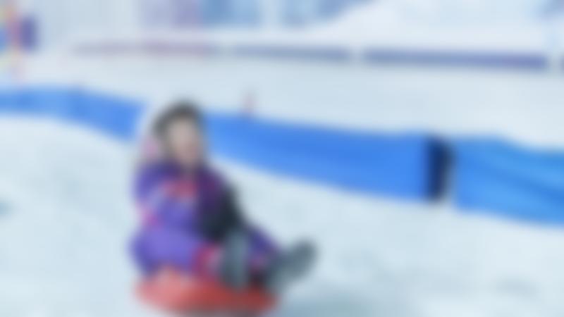 A girl sledding at The Snow Centre, Hemel Hempstead