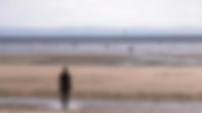 People on beach at Antony Gormleys Another Place in Liverpool
