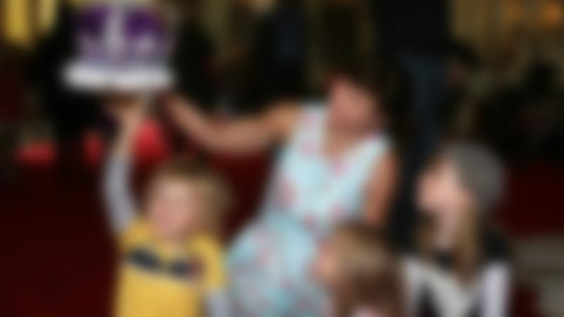 Family holding crown at Palace of Holyroodhouse in Edinburgh