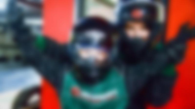 Two people wearing karting helmets celebrating at Scotkart Indoor Kart Racing Clydebank