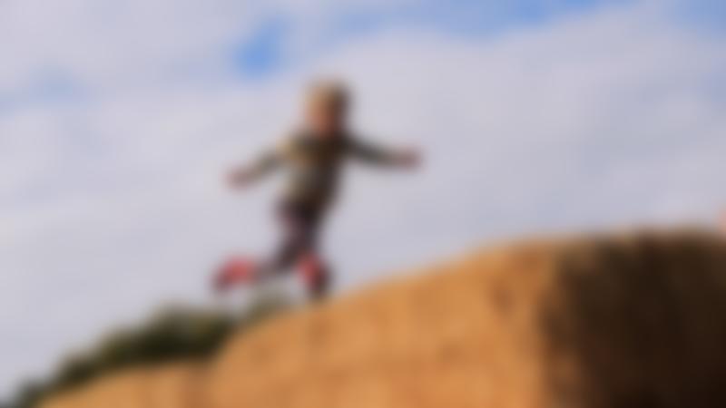 Boy running on hay at Baylham House Rare Breeds Farm in Ipswich