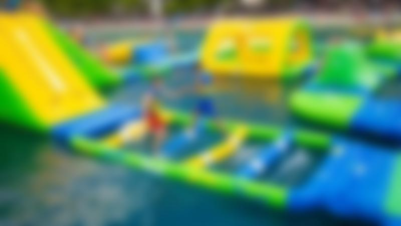 Two kids take on the inflatable hurdles at Cable and Wake