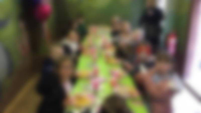 A group of kids eating party food at Reddish Vale Farm