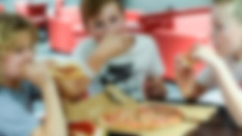Some kids eating pizza at TeamSport Indoor Karting Preston
