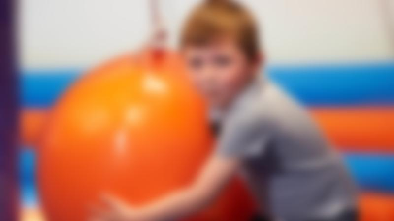 Boy with giant orange ball at Inflata Nation Newcastle
