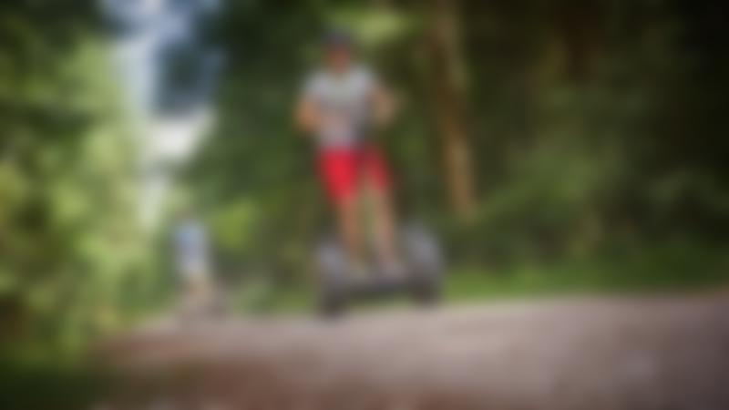Two people riding scooters at Go Ape Forest of Dean