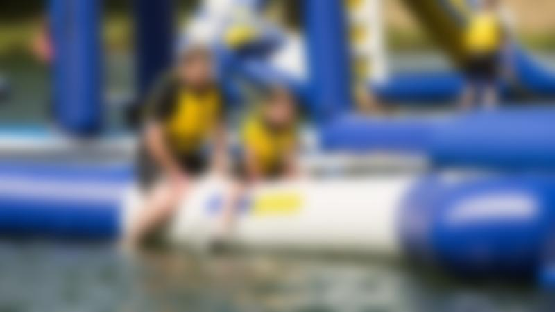 Dad and daughter on inflatable course at Aqua Park Rutland in Whitwell