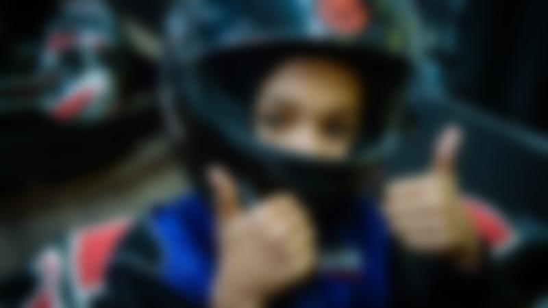A little girl smiling at TeamSport Indoor Karting Preston