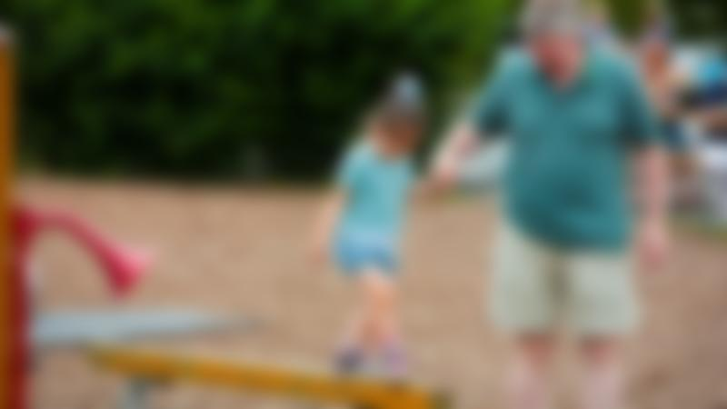 A little girl and her Dad in the park at The Hop Farm Family Park in Kent