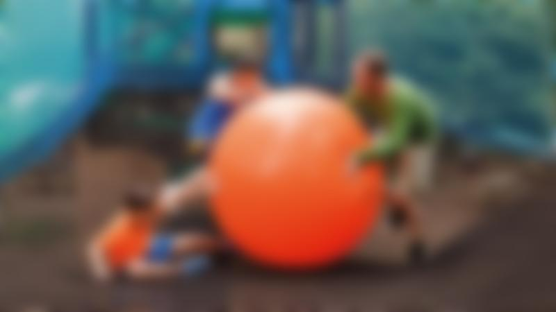 A family playing with a giant ball at Go Ape Black Park