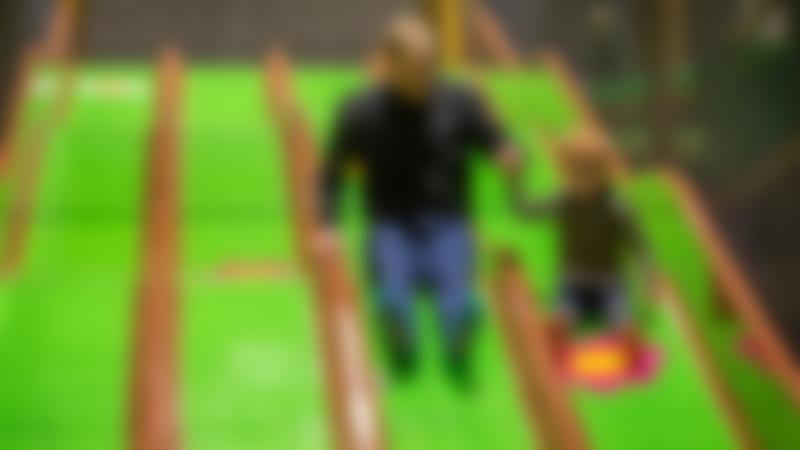A dad and a little boy going down a slide at Carerton Soft Play and Trampoline Park in Oxfordshire