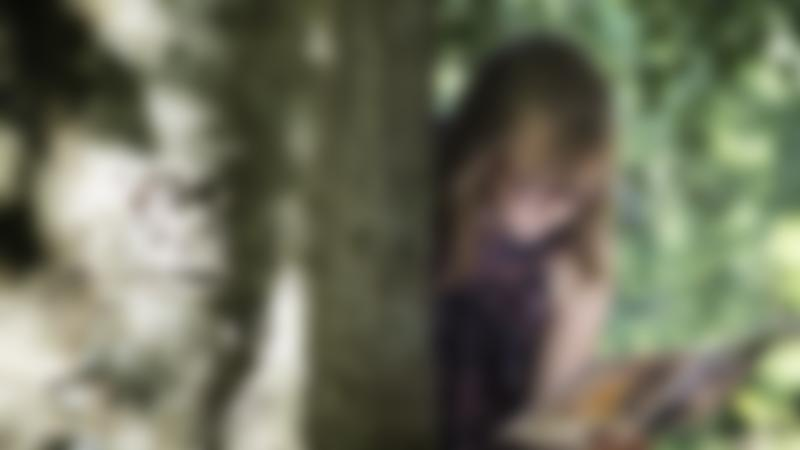 A girl looking round a tree doing a treasure trail