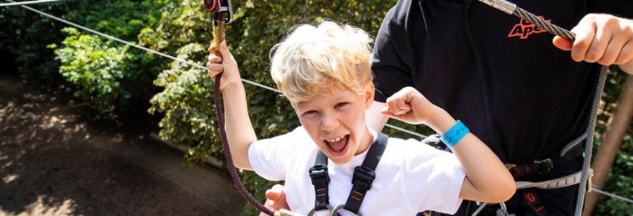 Happy blond boy raiding fist in victory at Go Ape