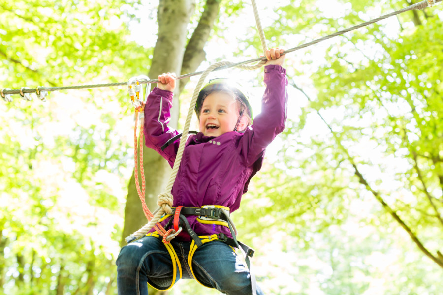 Girl in purple jacket hanging on a high ropes obstacle