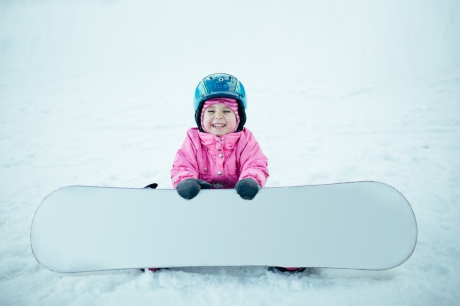 Little toddler girl with a snowboard