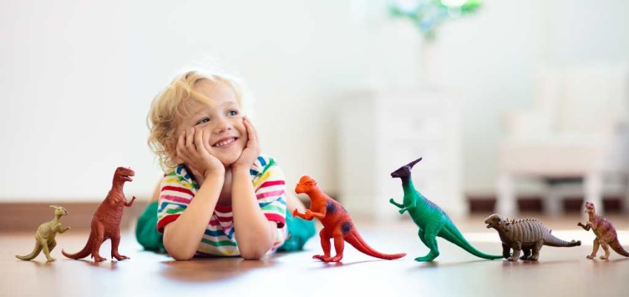 A little boy with toy dinosaurs