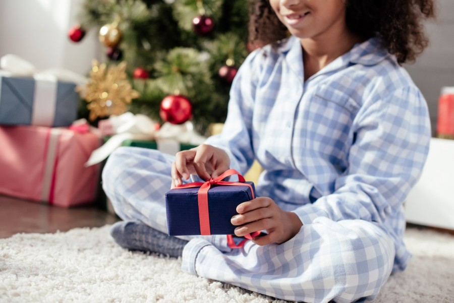 Girl in pyjamas opening a Christmas present