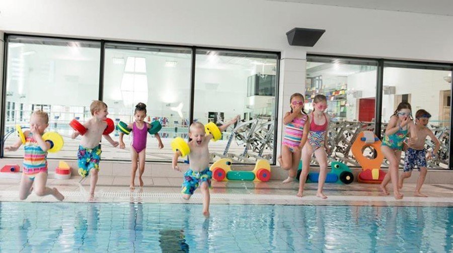 Kids leaping into an indoor pool.